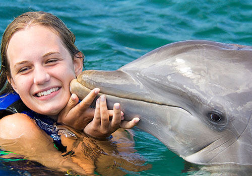 women being kissed by a dolphin at the dolphin experience Punta Cana